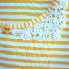 Børnetøj: Detalje af gul-hvid stribet T-shirt med blonde i halskant