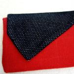 Clutches: ullaulla clutch rød med klap i blank sort. Clutchen er syet af møbelstof.
